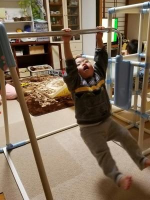 室内の鉄棒で遊ぶ孫